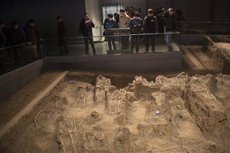 Journalists and visitors look at skeletons of victims of the 1937 Nanjing massacre at the Nanjing Massacre Museum during a media trip, in Nanjing