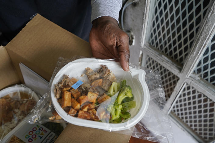 """Jackie Robinson shows the contents of meal boxes he received that were delivered by Revolution Foods in New Orleans on Thursday, Feb. 11, 2021. Robinson, a 66-year-old retired cook who once worked at a French Quarter restaurant in New Orleans, struggled to get by on his Social Security benefits before the pandemic, occasionally visiting a food pantry. But over the summer he signed up for a city-run delivery program and now gets two meals a day, seven days a week. """"Things were getting kind of tough, a little rough and ... I needed a little extra assistance,"""" he said. (AP Photo/Gerald Herbert)"""