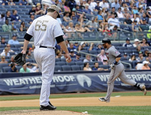 New York Yankees pitcher Phil Hughes reacts as Minnesota Twins' Ryan Doumit, right, rounds the bases after hitting a home run during the seventh inning of a baseball game Saturday, July 13, 2013, at Yankee Stadium in New York. (AP Photo/Bill Kostroun)