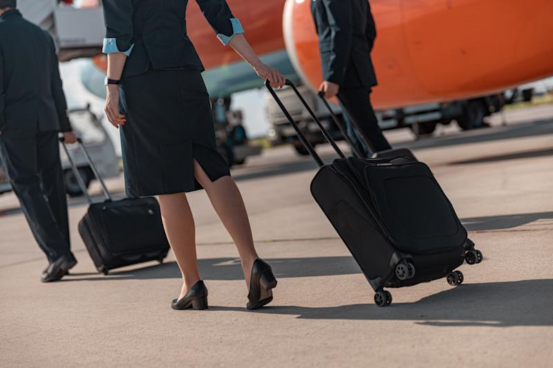 A flight attendant wheels a bag past aircraft on the ground.