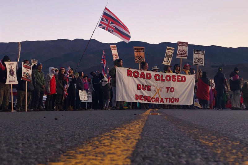 FILE - In this July 15, 2019, file photo, demonstrators block a road at the base of Hawaii's tallest mountain, in Mauna Kea, Hawaii, to protest the construction of a giant telescope on land that some Native Hawaiians consider sacred. The University of Hawaii's board is forming a task force to study the school's management of Mauna Kea's summit, which is currently at the center of long-running protests against the construction of a new telescope. (AP Photo/Caleb Jones)