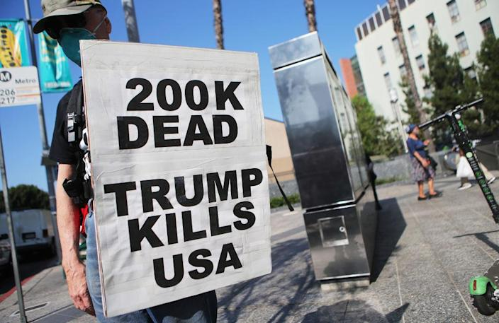 A protester holds a sign reading '200K Dead Trump Kills USA' at a march against 'Death, Lies and Fascism' on September 21, 2020 in Los Angeles, California. Demonstrators protested against President Donald Trump's handling of the COVID-19 pandemic as the U.S. surpasses 204,000 deaths from the coronavirus. (Photo by Mario Tama/Getty Images)