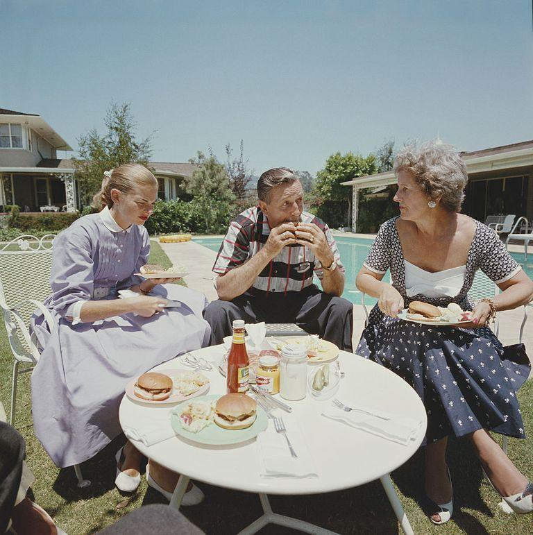 <p>Walt Disney bites into a hamburger while he, his wife Lillian, and their daughter enjoy a poolside lunch in 1955. </p>