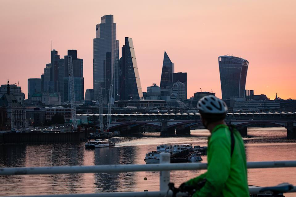 Early morning light bathes the skyscrapers of the City of London financial district, at the start of a week in which the UK is expected to bask in temperatures of more than 30C.