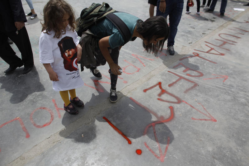 A child wearing a t-shirt with the image of Turkeys' founder Mustafa Kemal Ataturk looks on as a protester writes a slogan that says: 'Opposition', on the pavement of Taksim Square in Istanbul, Friday, June 7, 2013. Erdogan took a combative stance on his closely watched return to the country early Friday, telling supporters who thronged to greet him that the protests that have swept the country must come to an end. (AP Photo/Kostas Tsironis)