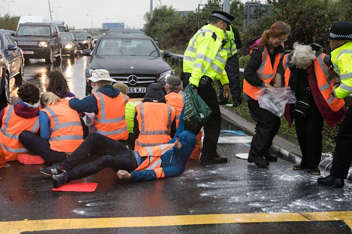 Metropolitan Police officers remove Insulate Britain climate activists from a M25 slip road at Junction 14 close to Heathrow airport which they had blocked as part of a campaign intended to push the UK government to make significant legislative change to start lowering emissions on 27th September 2021 in Colnbrook, United Kingdom. The activists are demanding that the government immediately promises both to fully fund and ensure the insulation of all social housing in Britain by 2025 and to produce within four months a legally binding national plan to fully fund and ensure the full low-energy and low-carbon whole-house retrofit, with no externalised costs, of all homes in Britain by 2030. (photo by Mark Kerrison/In Pictures via Getty Images)