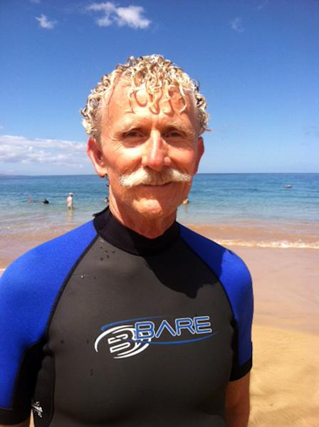 In this Aug. 15, 2013 photo provided by Nicholas Grisaffi, Rick Moore poses at Palauea Beach in Makena on the island of Maui, Hawaii, a day after he jumped into the water to rescue a shark attack victim who lost her arm. A woman who lost her arm in a Maui shark attack kept repeating that she was going to die, said Rick Moore, a California high school teacher who jumped into the water to save her. (AP Photo/Nicholas Grisaffi)