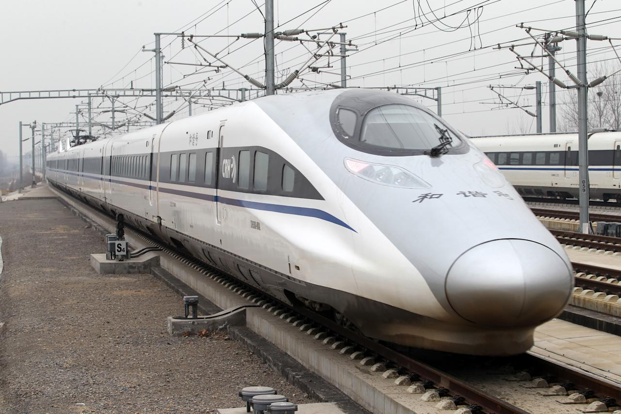 The high speed train that runs on the new 2,298-kilometre (1,425-mile) line between Beijing and Guangzhou runs into Xuchang East Station in Xuchang, central China's Henan province on December 26, 2012. China started service on December 26 on the world's longest high-speed rail route, the latest milestone in the country's rapid and -- sometimes troubled -- super fast rail network. The opening of this new line means passengers will be whisked from the capital to the southern commercial hub in just eight hours, compared with the 22 hours previously required.   CHINA OUT   AFP PHOTO