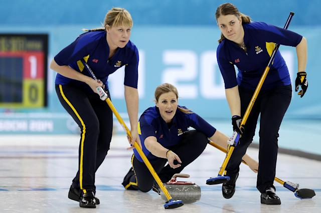 Sweden's Christina Bertrup, center, releases the rock for sweepers Maria Prytz, left, and Maria Wennerstroem, right, during the women's curling competition against Great Britain at the 2014 Winter Olympics, Monday, Feb. 10, 2014, in Sochi, Russia. (AP Photo/Wong Maye-E)