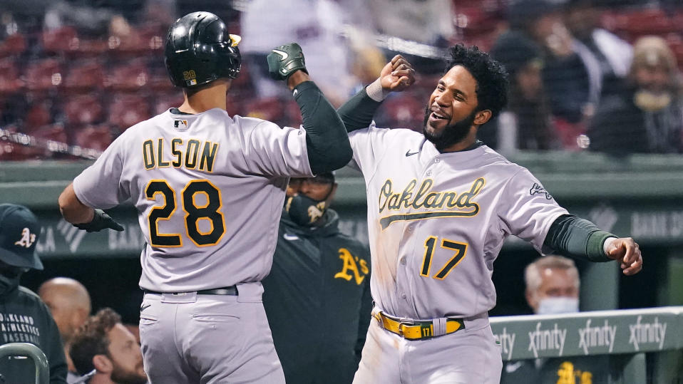 Oakland Athletics' Matt Olson, left, is congratulated by Elvis Andrus (17) after his solo home run off Boston Red Sox starting pitcher Eduardo Rodriguez during the sixth inning of a baseball game, Wednesday, May 12, 2021, in Boston. (AP Photo/Charles Krupa)