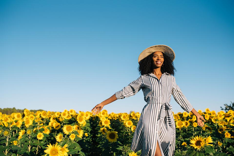 Happy young black woman walking in a sunflower field