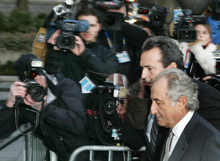 Accused swindler Bernard Madoff (bottom) enters the Manhattan federal court house in New York March 12, 2009. Madoff, accused of running the biggest fraud in Wall Street history, is expected to plead guilty on Thursday in what is shaping up to be a courtroom drama featuring denunciations by investors and a renewed push by prosecutors to jail him immediately.   REUTERS/Shannon Stapleton   (UNITED STATES BUSINESS CONFLICT SOCIETY)