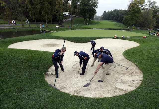 Grounds crew members work in a bunker on the ninth hole following a rain delay during the foursome matches at the Presidents Cup golf tournament at Muirfield Village Golf Club Friday, Oct. 4, 2013, in Dublin, Ohio. (AP Photo/Darron Cummings)