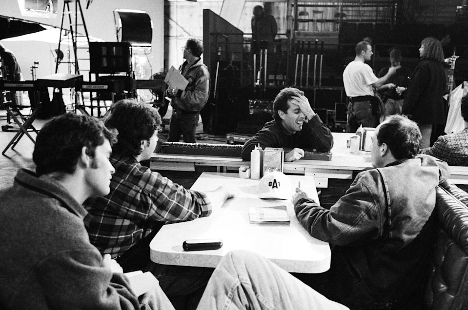 <p>Seinfeld meets with the show's writers, who are seen here sitting in the booths on the set of the diner. </p>