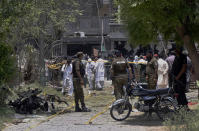Police officers, investigators and rescue workers gather at the site of explosion, in Lahore, Pakistan, Wednesday, June 23, 2021. A powerful explosion ripped through a residential area in the eastern city of Lahore on Wednesday, killing some people and injuring some others, police and rescue officials said. (AP Photo/K.M. Chaudary)