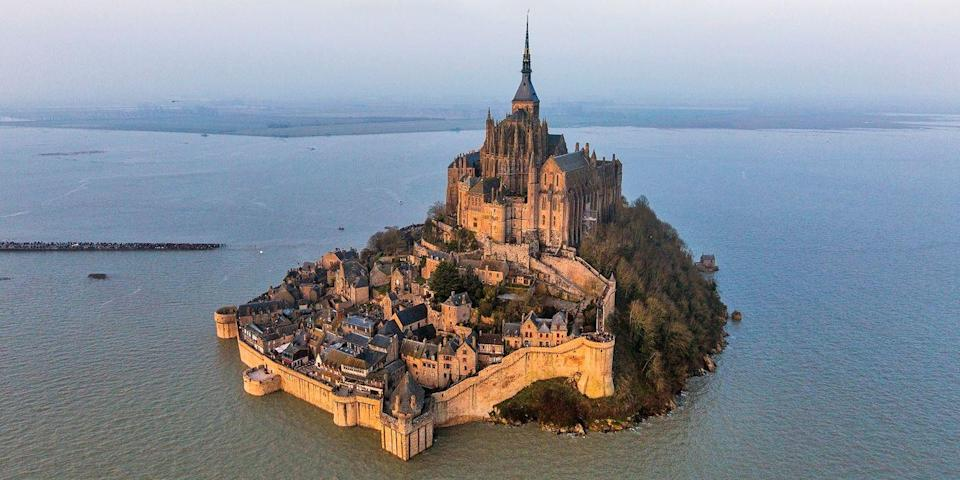 """<p><a href=""""https://www.tripadvisor.com/Attraction_Review-g196646-d207387-Reviews-Abbaye_du_Mont_Saint_Michel-Mont_Saint_Michel_Manche_Basse_Normandie_Normandy.html"""" rel=""""nofollow noopener"""" target=""""_blank"""" data-ylk=""""slk:Mont Saint-Michel"""" class=""""link rapid-noclick-resp"""">Mont Saint-Michel</a>, the tiny medieval walled city in Normandy, never fails to take your breath away. Built on a granite outcrop in the Couesnon River's flats and dominated by a massive Gothic abbey, it became a UNESCO World Heritage Site in 1979. The area is known for its tidal activity, and during the spring and autumn equinoxes, water can surround the structure, creating quite the photo op.</p>"""