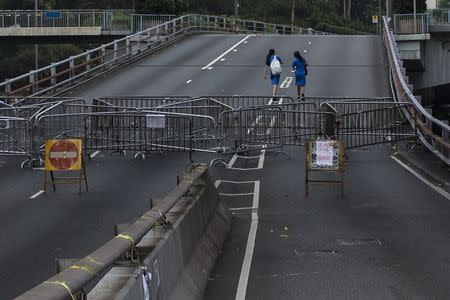 Secondary school students walk on a highway past a roadblock, part of an area blocked off by protesters of the Occupy Central movement, on their way to school in Hong Kong October 7, 2014. REUTERS/Tyrone Siu