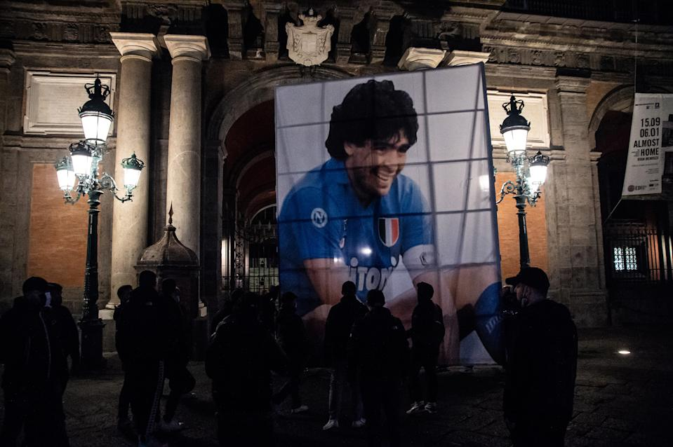NAPLES, ITALY - NOVEMBER 26: A parade of supporters in Piazza del Plebiscito, where a choreography with red smoke bombs was set up to remember Diego Armando Maradona on November 26, 2020 in Naples, Italy. Diego Armando Maradona died at 60 after a cardiocirculatory arrest while he was at his house in Tigre, Argentina, where he was spending his convalescence after brain surgery three weeks before. (Photo by Ivan Romano/Getty Images)