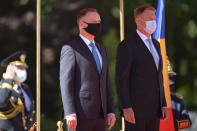 Polish President Andrzej Duda, left, stands with Romanian President Klaus Iohannis during the welcoming ceremony at the Cotroceni presidential palace in Bucharest, Romania, Monday, May 10, 2021. (AP Photo/Alexandru Dobre)