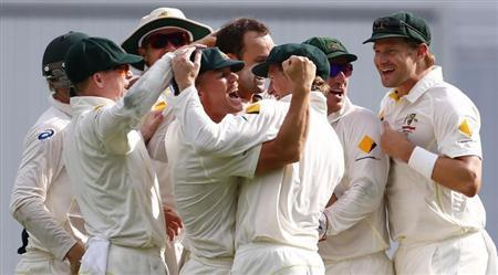 Australia's team celebrate with David Warner (C) celebrate after Warner took the catch to dismiss England's Matt Prior during the fourth day's play of the first Ashes cricket test match in Brisbane November 24, 2013. REUTERS/David Gray