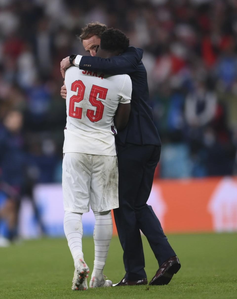 England's manager Gareth Southgate, right, hugs England's Bukayo Saka after the penalty shootout of the Euro 2020 soccer final match between England and Italy at Wembley stadium in London, Sunday, July 11, 2021. (Laurence Griffiths/Pool via AP)