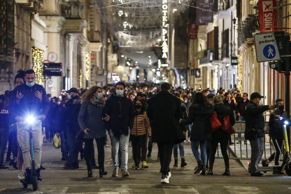 People stroll in Via del Corso shopping street, downtown Rome, Saturday, Dec. 5, 2020. Earlier in the week, Italy's Premier Giuseppe Conte signed a decree sharply limiting travel between regions on Dec. 21 till after the Jan. 6 national Epiphany Day holiday. (Cecilia Fabiano/LaPresse via AP)