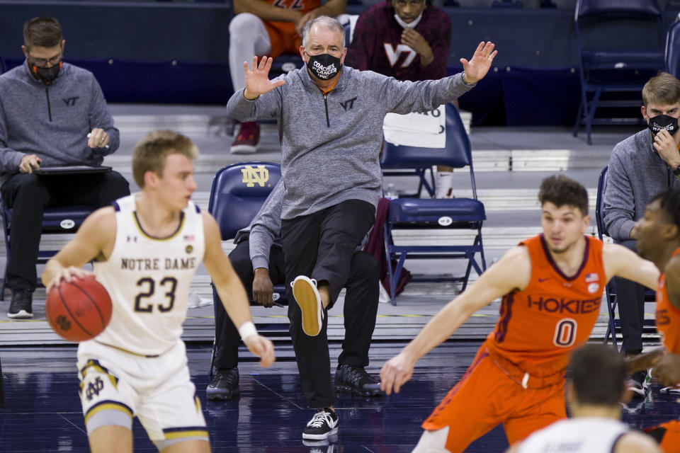 Virginia Tech coach Mike Young makes a kicking motion during the first half of the team's NCAA college basketball game against Notre Dame on Wednesday, Jan. 27, 2021, in South Bend, Ind. (AP Photo/Robert Franklin)
