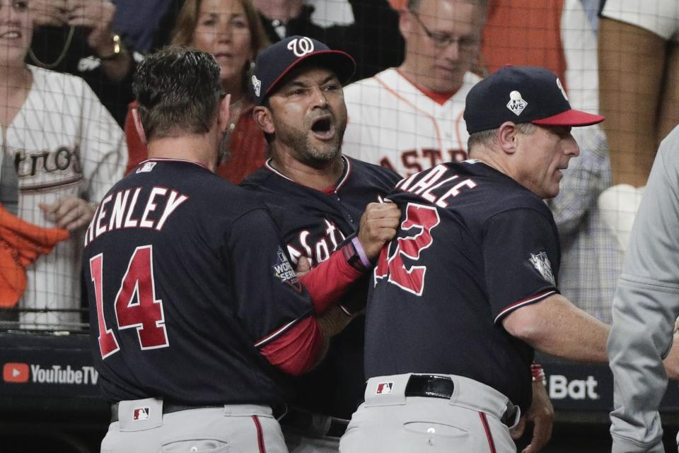 Washington Nationals manager Dave Martinez has to be restrained after being ejected for arguing an interference call during the seventh inning of Game 6 of the baseball World Series against the Houston Astros Tuesday, Oct. 29, 2019, in Houston. (AP Photo/David J. Phillip)