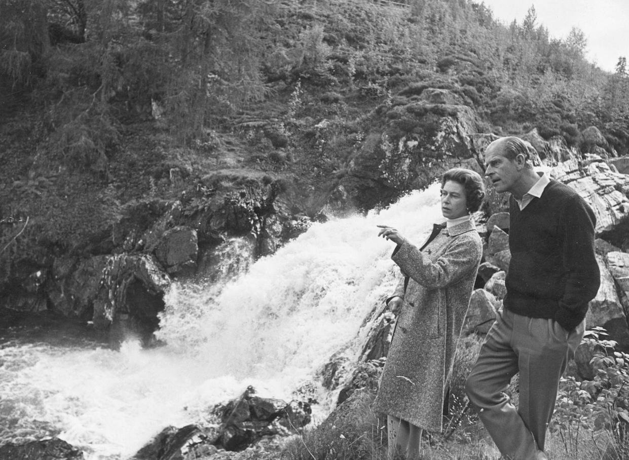October 1972:  Queen Elizabeth II and Prince Philip, Duke of Edinburgh by a waterfall in the grounds of Balmoral Castle, Scotland. Queen Victoria's husband, Prince Albert, purchased Balmoral Castle in 1846, and the small castle which stood in the 7,000 hectare wooded estate was redeveloped in the 1850s.The granite building was designed by Aberdeen architect William Smith with suggestions from Albert himself, who decided the interior decoration should represent a Highland shooting box with tartan or thistle chintzes, and walls decorated with trophies and weapons. Queen Victoria often visited the Highlands with her family, especially after Albertfs death in 1861, and Balmoral is still a popular retreat for the present royal family.  (Photo by Fox Photos/Getty Images)