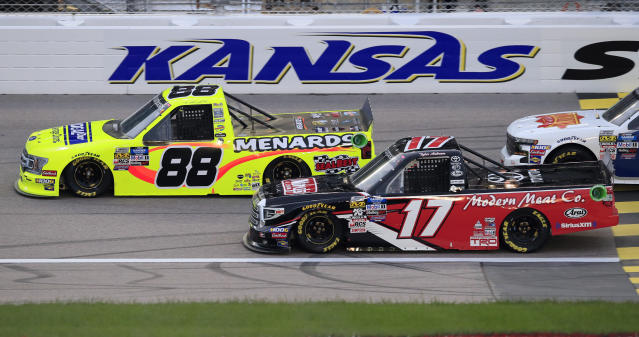 Matt Crafton (88) and Tyler Ankrum (17) charge into the first lap of the NASCAR Truck Series auto race at Kansas Speedway in Kansas City, Kan., Friday, May 10, 2019. (AP Photo/Orlin Wagner)