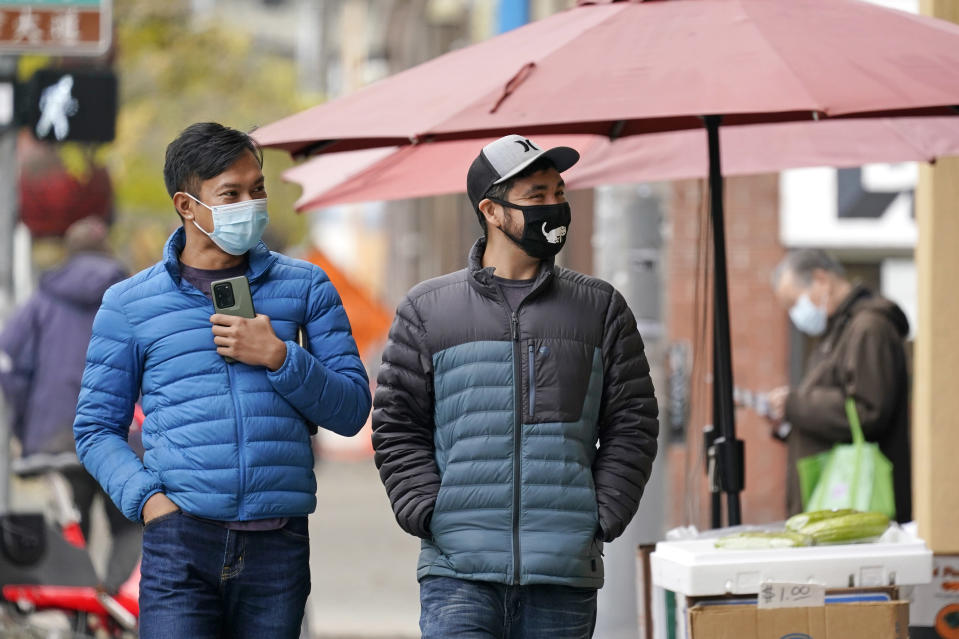 Pedestrians wearing masks walk past a small grocery store in the Chinatown-International District Thursday, Nov. 12, 2020, in Seattle. Washington state and county health officials have warned of a spike in coronavirus cases across the state, and pleaded with the public to take the pandemic more seriously heading into the winter holidays. (AP Photo/Elaine Thompson)