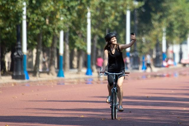 A cyclist takes a selfie on the Mall in central London on August 9