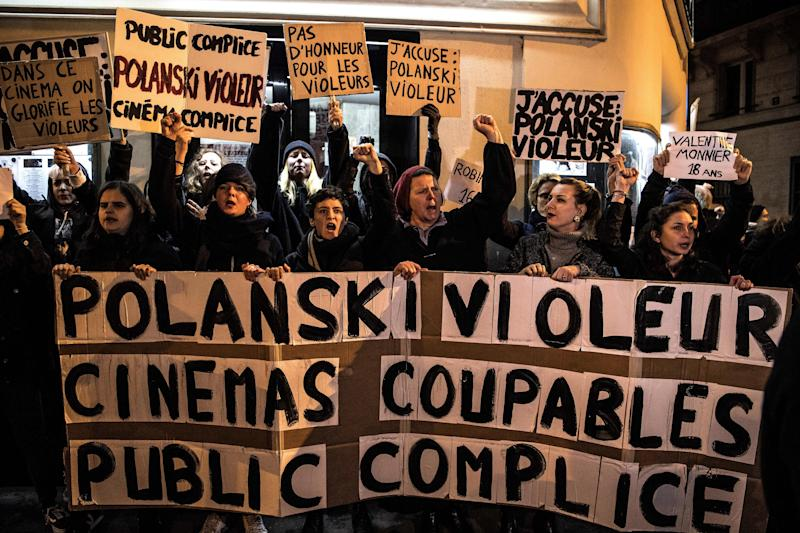"Demonstrators hold banners reading ""Polanski rapist, cinemas guilties, public accomplice"" during a protest against French-Polish film director Roman Polanski outside the ""Champo"" cinema hall in Paris on November 12, 2019. - Interviews to promote Polanski's new film ""An Officer and a Spy"" have been either cancelled or pulled after a new rape allegation against the controversial director on November 8. (Photo by Christophe ARCHAMBAULT / AFP) (Photo by CHRISTOPHE ARCHAMBAULT/AFP via Getty Images)"