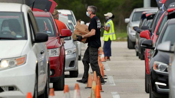 PHOTO: Workers and volunteers help load cars with food at a San Antonio Food Bank drive-through distribution in San Antonio, April 7, 2020.  (Eric Gay/AP, FILE)