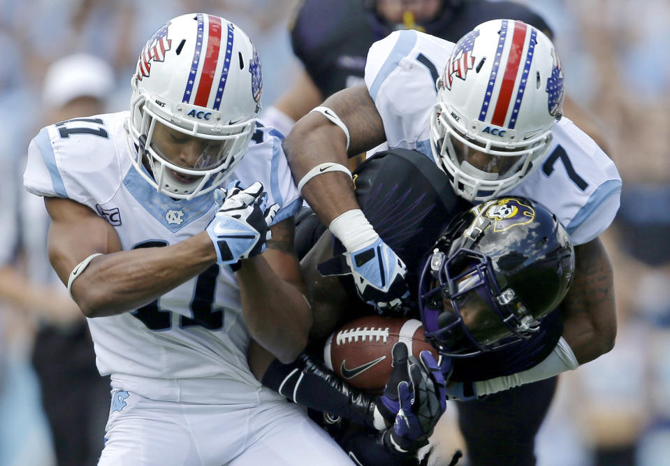 North Carolina's Tim Scott (7) and Malik Simmons (11) tackle East Carolina's Justin Hardy (2) during the first half of an NCAA college football game in Chapel Hill, N.C., Saturday, Sept. 28, 2013. (AP Photo/Gerry Broome)