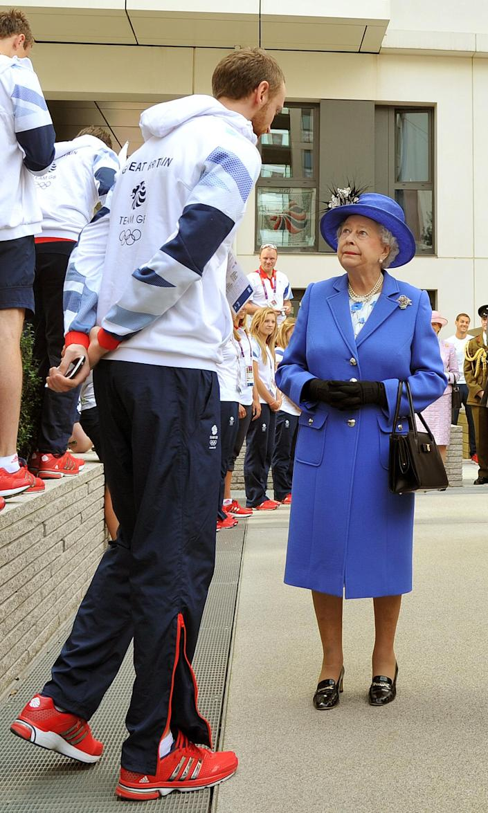 Queen Elizabeth II meets one of the taller members of the Great Britain team, as she tours the Athletes Village at the Olympic Park in London, Saturday July 28, 2012. (AP Photo/John Stillwell, Pool)