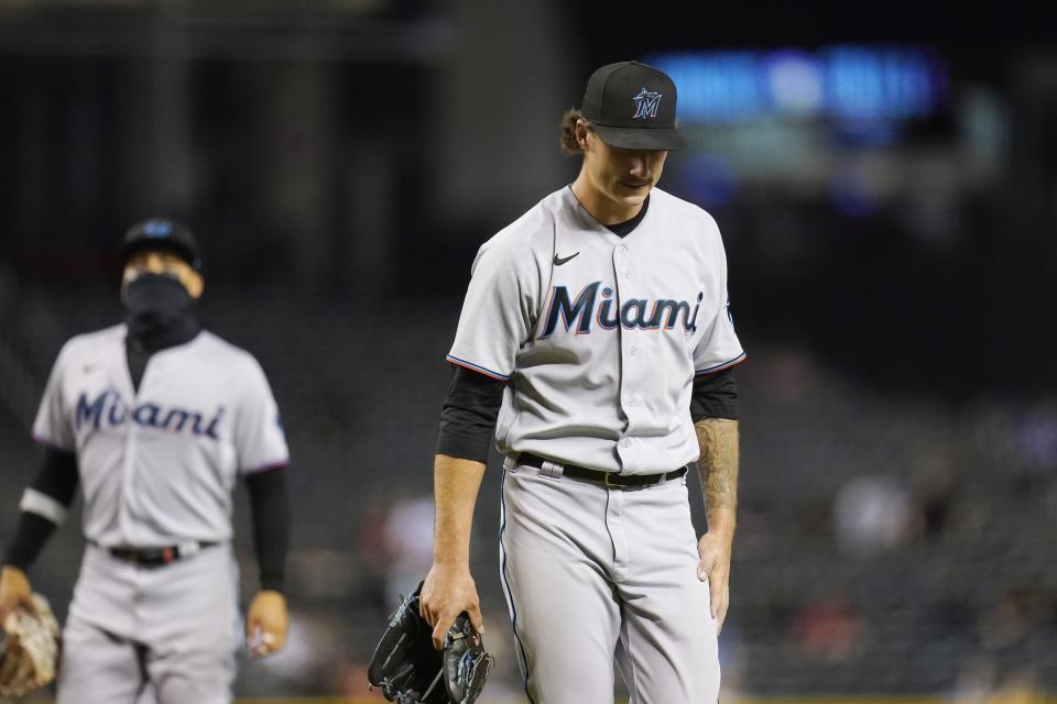 Miami Marlins starting pitcher Jordan Holloway, right, walks off the field as he is replaced while Marlins second baseman Isan Diaz, left, looks on during the fourth inning of a baseball game against the Arizona Diamondbacks, Monday, May 10, 2021, in Phoenix. (AP Photo/Ross D. Franklin)