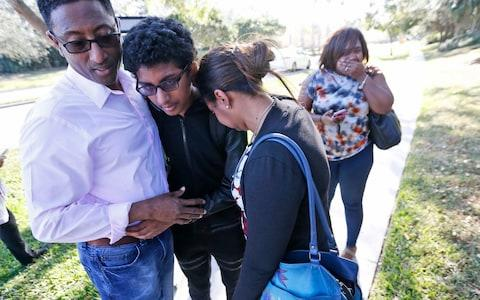 Family members embrace after a student walked out from Marjory Stoneman Douglas High School