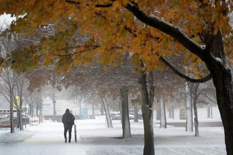 People navigate snow-covered sidewalks in the Humboldt Park neighborhood on November 11, 2019, in Chicago, Illinois. Forecasters are calling for three to six inches of snow to fall in the Chicago area by mid-day today and temperatures are expected to fall to around ten degrees by tomorrow.