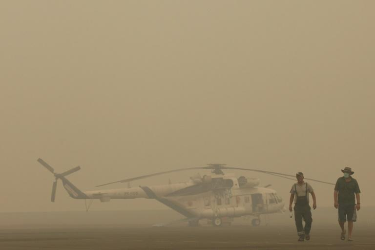 A helicopter crew deployed for water bombing by the National Disaster Management Agency walk past their grounded aircraft due to thick haze in Palembang on Indonesia's Sumatra island on September 30, 2015