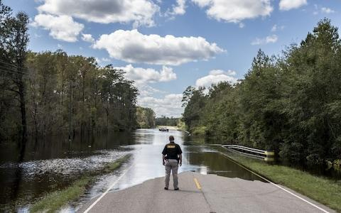 A Pender County Sheriff looks out over a flooded road - Credit: Alex Wroblewski/Bloomberg