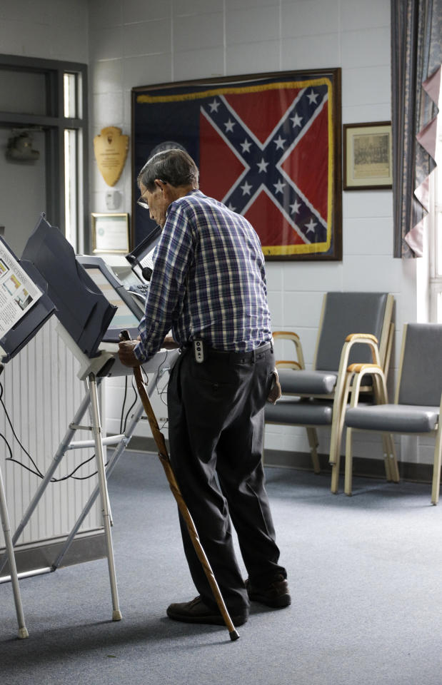 The 1956 Georgia state flag is displayed in a frame as George Farr votes at the Chickamauga Civic Center on Tuesday, May 22, 2018, in Chickamauga, Ga. In Georgia's gubernatorial primaries Tuesday, Democrats were guaranteed the party's first female nominee for the office while the Republican contest centered largely on who loved guns the most and was toughest on immigration. (Doug Strickland/Chattanooga Times Free Press via AP)