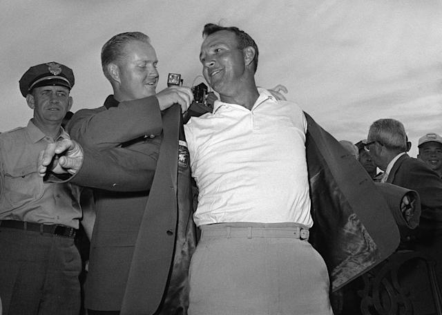 FILE - In this April 12, 1964 file photo, Arnold Palmer, right, slips into his green jacket with help from Jack Nicklaus after winning the Masters golf championship, in Augusta, Ga. Fifty years ago, Palmer won the Masters for the fourth time. It was his seventh major. He was 34, the King. (AP Photo/File)