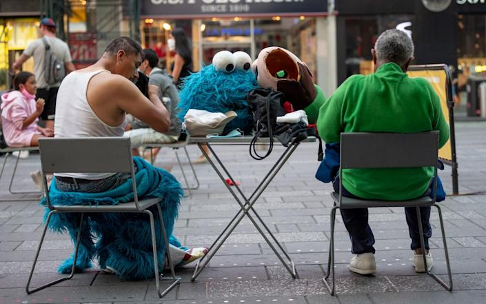 The head of a Cookie Monster costume is put on a table next to a person removing their costume in Times Square as the city moves into Phase 3 of re-opening following restrictions imposed to curb the coronavirus pandemic on July 7, 2020 in New York City - Alexi Rosenfeld/Getty Images North America