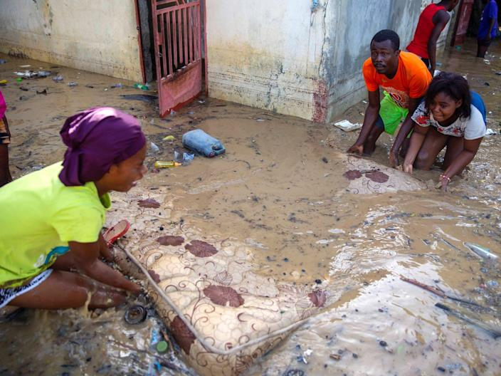 """Neighbors help Lafaille Katia (left) pick up a mattress at her flooded house the day after Tropical Storm Laura in Port-au-Prince, Haiti, August 24, 2020. <p class=""""copyright""""><a href=""""https://newsroom.ap.org/detail/HaitiTropicalWeather/46506ff6bd4e4b6e8936ff4d123d93d8/photo?Query=tropical%20storm%20laura&mediaType=photo&sortBy=arrivaldatetime:desc&dateRange=Anytime&totalCount=48&currentItemNo=14"""" rel=""""nofollow noopener"""" target=""""_blank"""" data-ylk=""""slk:Dieu Nalio Chery/AP Photo"""" class=""""link rapid-noclick-resp"""">Dieu Nalio Chery/AP Photo</a></p>"""
