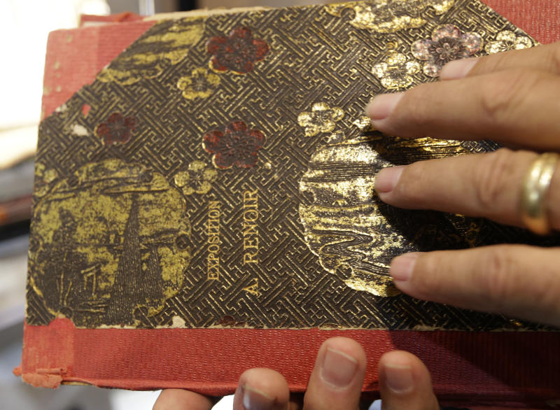 In this photo made Friday, Aug. 16, 2013, Brian Roughton, managing director of fine art at the Heritage Auctions, holds the personal note book of Pierre-Auguste Renoir in Dallas. The French artist's personal archive will be up for sale in New York City in September. (AP Photo/LM Otero)