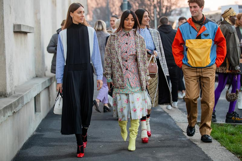 MILAN, ITALY - JANUARY 12: Giorgia Tordini wearing black white blue striped multi colored dress, Amina Muaddi wearing mixed pattern, Gilda Ambrosio wearing Prada bag, yellow skirt, striped button shirt, plaid coat and Marc Forne wearing Prada jacket and brown pants seen outside Prada during Milan Fashion Week Fall/Winter 2020/2021 on January 12, 2020 in Milan, Italy. (Photo by Christian Vierig/Getty Images)