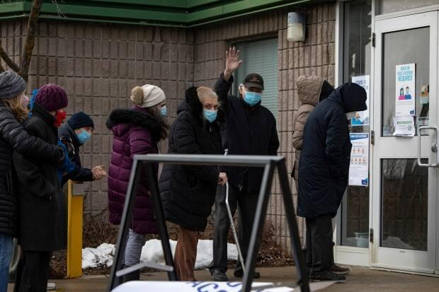 Senior citizens, some accompanied by loved ones, line up outside the Richmond Green Sports Centre during the first day of COVID vaccinations for those age 80-plus in the general public on March 1. (Evan Mitsui/CBC - image credit)
