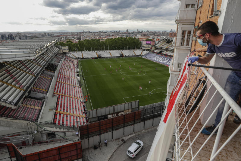A soccer supporter watches from a balcony the second-division game match between Rayo Vallecano and Albacete in Madrid, Spain, Wednesday, June 10, 2020. With virtual crowds, daily matches and lots of testing for the coronavirus, soccer is coming back to Spain. The Spanish league resumes this week more than three months after it was suspended because of the pandemic, becoming the second top league to restart in Europe. The Bundesliga was first. The Premier League and the Italian league should be next in the coming weeks. (AP Photo/Manu Fernandez)