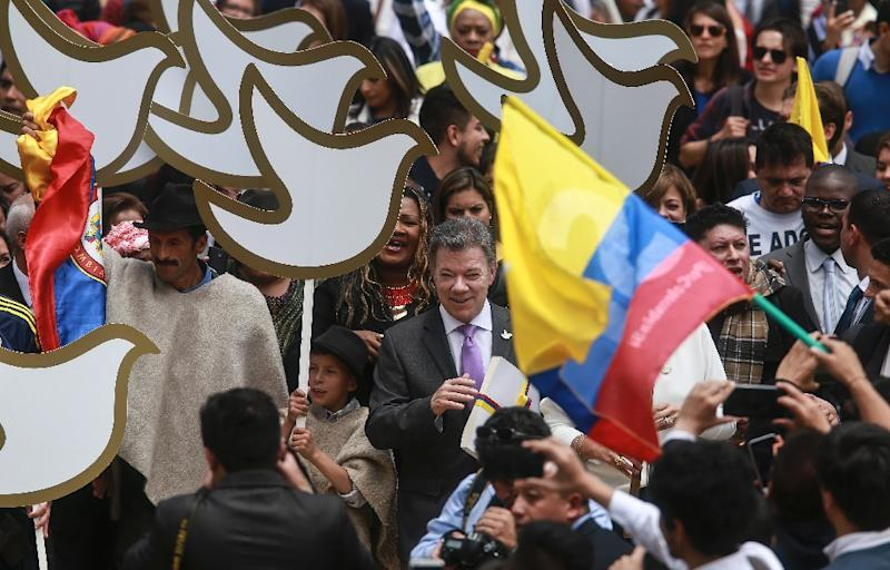 Colombian President Juan Manuel Santos (C) holds a copy with the final text of the peace agreement with the Revolutionary Armed Forces of Colombia (FARC) guerrillas, on his way to the National Congress in Bogota on August 25, 2016 (AFP Photo/Ivan Valencia)